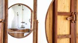 Looking through large round wooden doorway at a wooden bathtub and rain shower in the bathroom of the Hobbit Villa at the Mala Dhara Eco Resort and Yoga Retreat Center in chiang Mai Thailand.