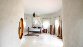 View along a curved adobe walls and round wooden doorway of the bed in the Hobbit Villa at the Chiang Mai Mala Dhara Eco Resort & Yoga Retreat Center, adorned with a hand made cotton mosquito net and surrounded by carefully chosen wooden furniture.