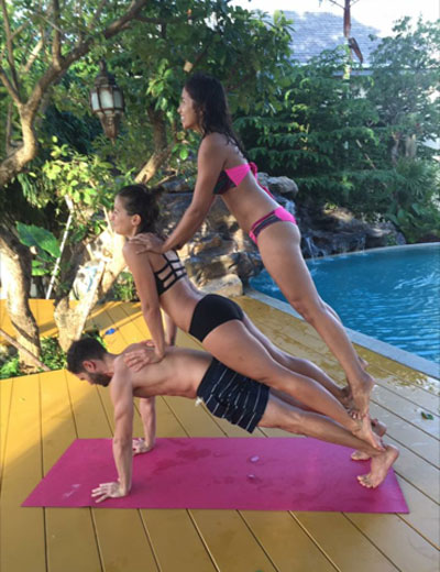 Three yoga students on the Wild Rose Yoga and Pranaya Yoga Teacher Training at the Mala Dhara Eco Resort in the Doi Saket area of Chiang Mai, Thailand doing some acro yoga poolside.