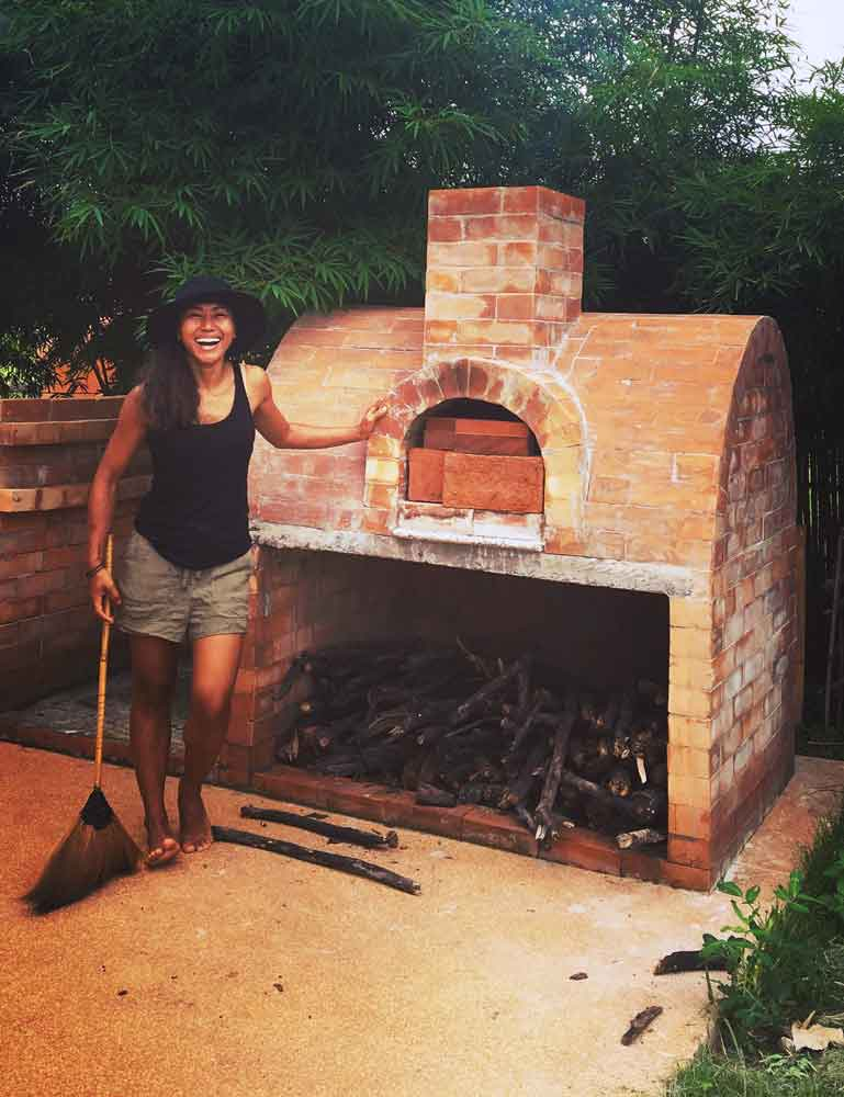 Ploy is standing next to the brick wood fired oven at the Mala Dhara Eco Resort in Chiang Mai with her broom and big smile.
