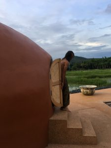 Man emerging after a traditional Thai herbal steam sauna with rice fields in the backround at the Mala Dhara Resort in Chiang Mai